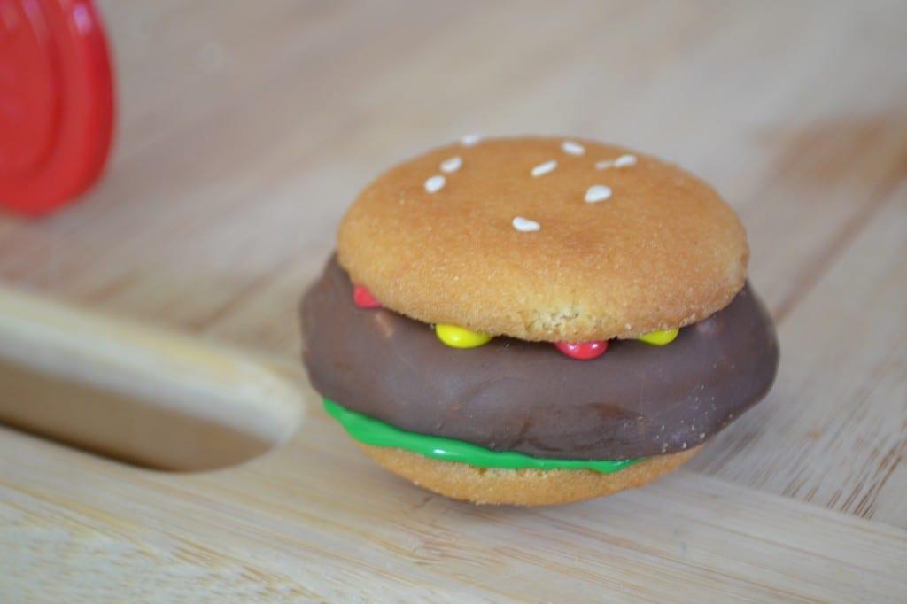A hamburger cookie on a cutting board